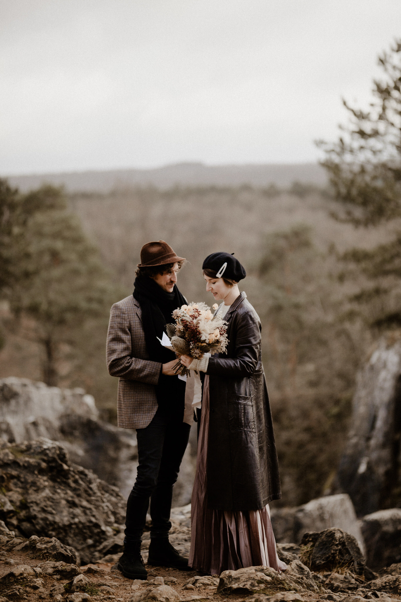 A lovely view of a couple eloping in the foresty hills of the Ardennes, while holding their flowers