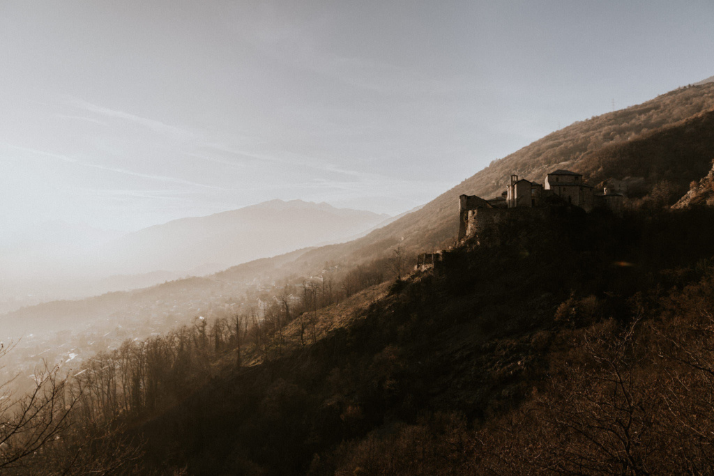 Hazy view of the fairytale Quart Castle on a hillside in Val d'Aosta, Italy