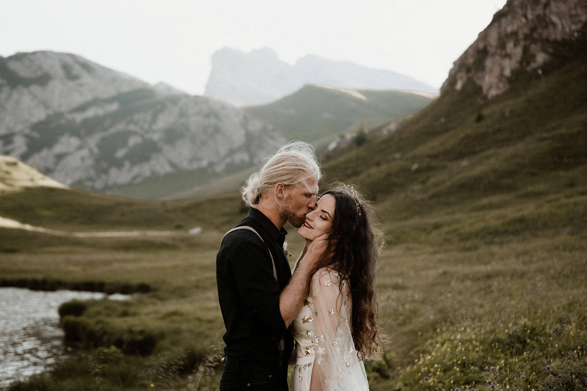 A tall groom gently kisses his girl, while standing in the middle of the Dolomite mountains for their elopement