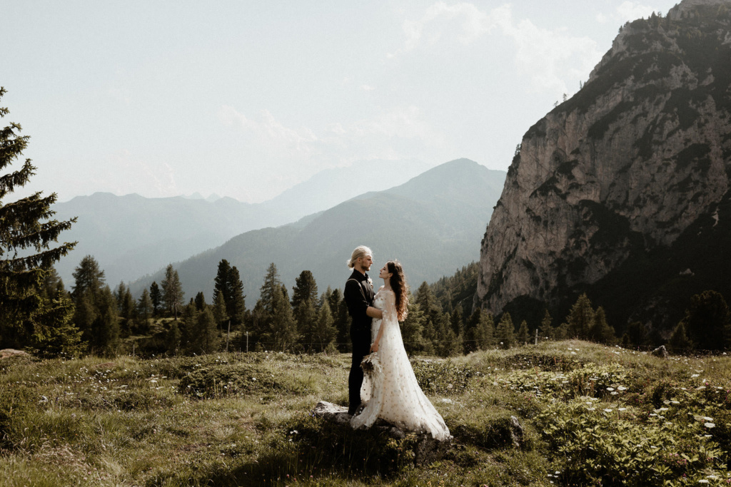 A dream elopement of a couple on an alpine meadow with trees and the Dolomite mountains in the background