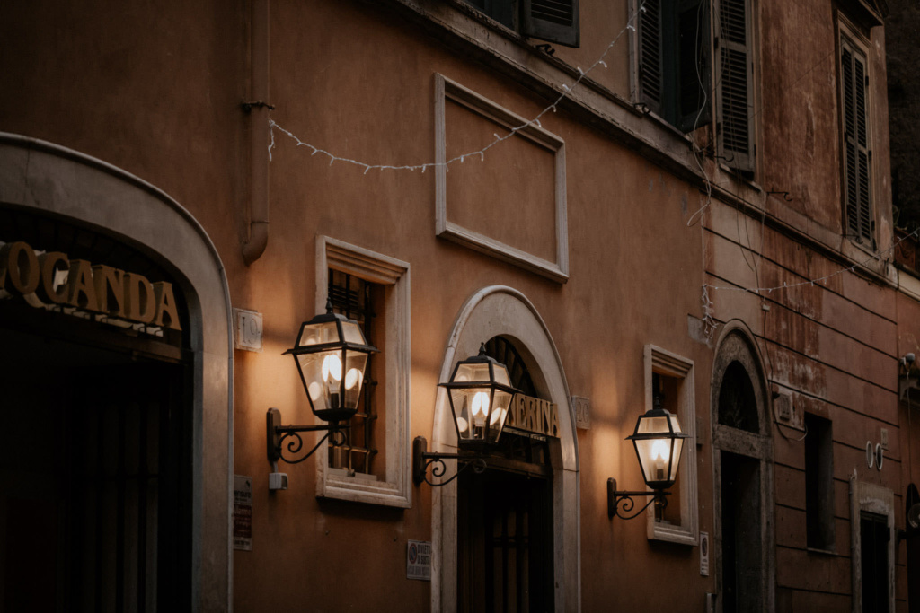Close up of street lights and fairy lights on a terracotta building in the streets of Trastevere, Rome