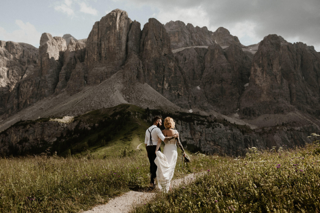 An elopement couple are walking intimately beneath the mountains of Passo Gardena in the alpine Dolomites of Italy
