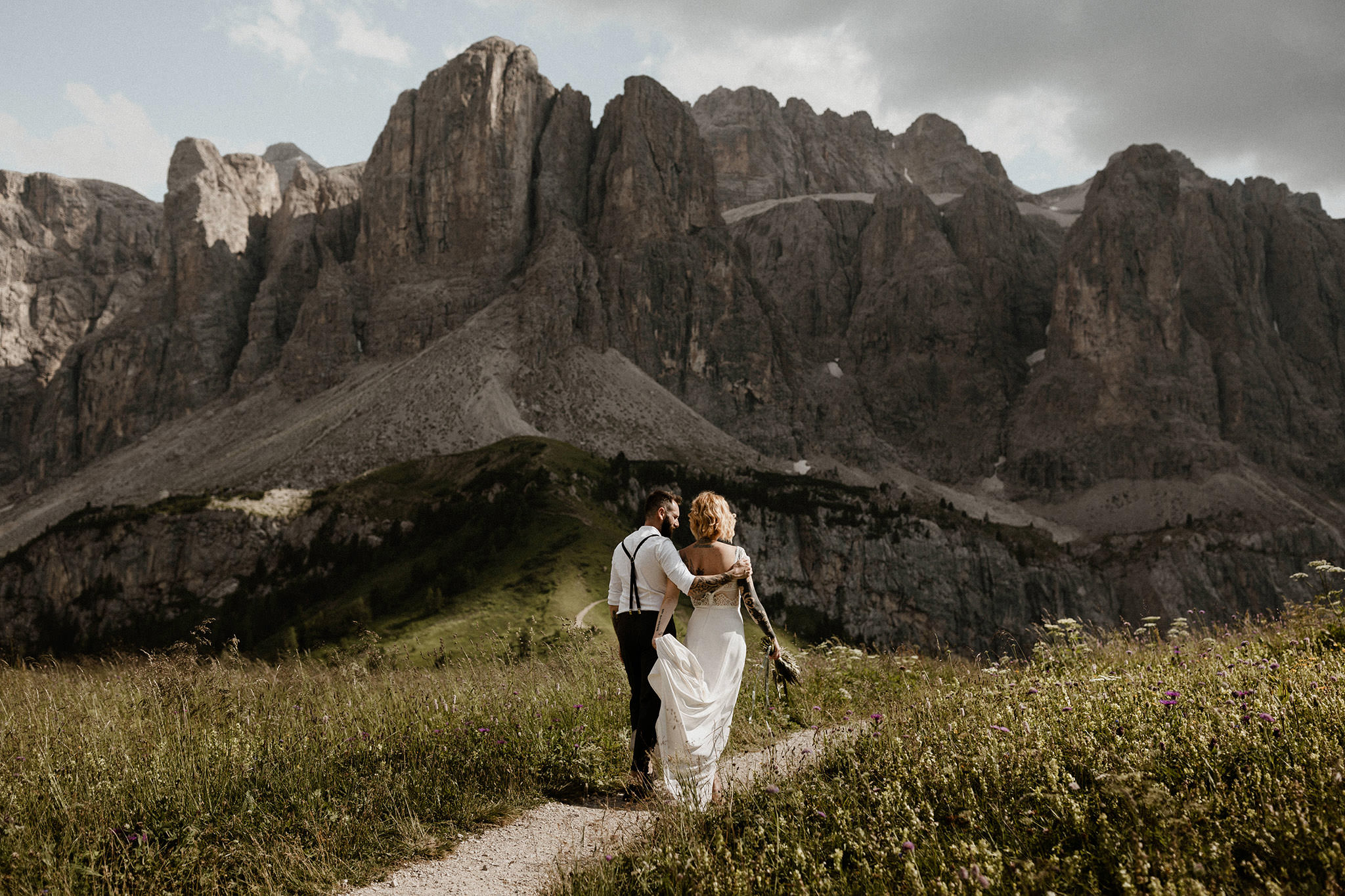 An freshly married couple are walking intimately beneath the mountains of Passo Gardena in the alpine Dolomites of Italy