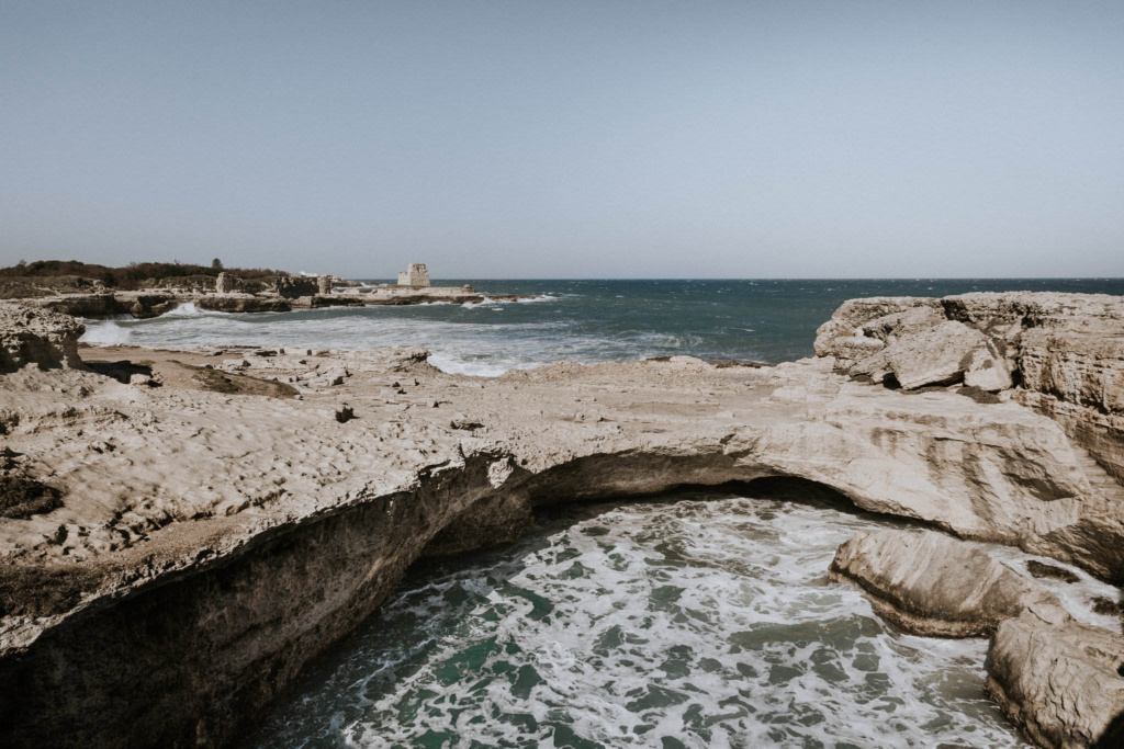The turquoise sea and sandy rock formations on the Puglia coastline, Italy