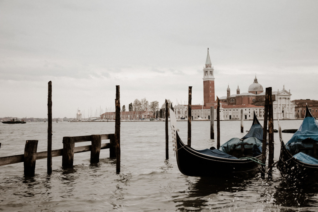 Close up view of floating gondolas tied up on a canal in Venice, with the Chiesa di San Giorgio in the background