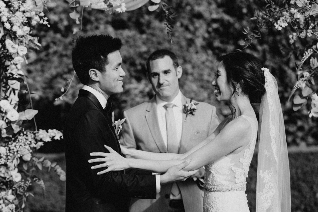 Black and white shot of a newly married couple under a flower arch having a symbolic ceremony in Tuscany, Italy.