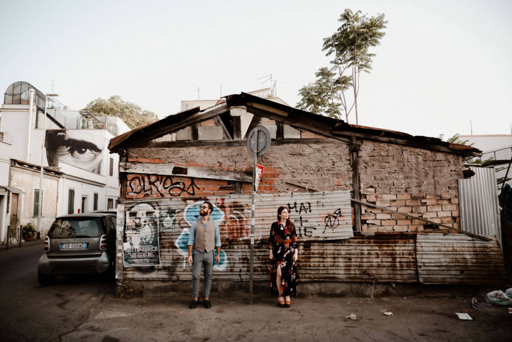 A couple stood in front of a graffiti-covered building on the streets of the Pigneto neighbourhood, Rome