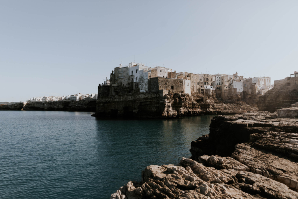 A view of white houses of Polignano a Mare, with the sparkling sea and rocks in the foreground