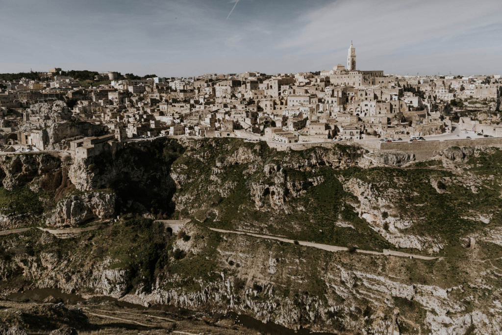 Wide view of sun-bleached Matera City on the edge of a canyon on the Gravina River, Italy