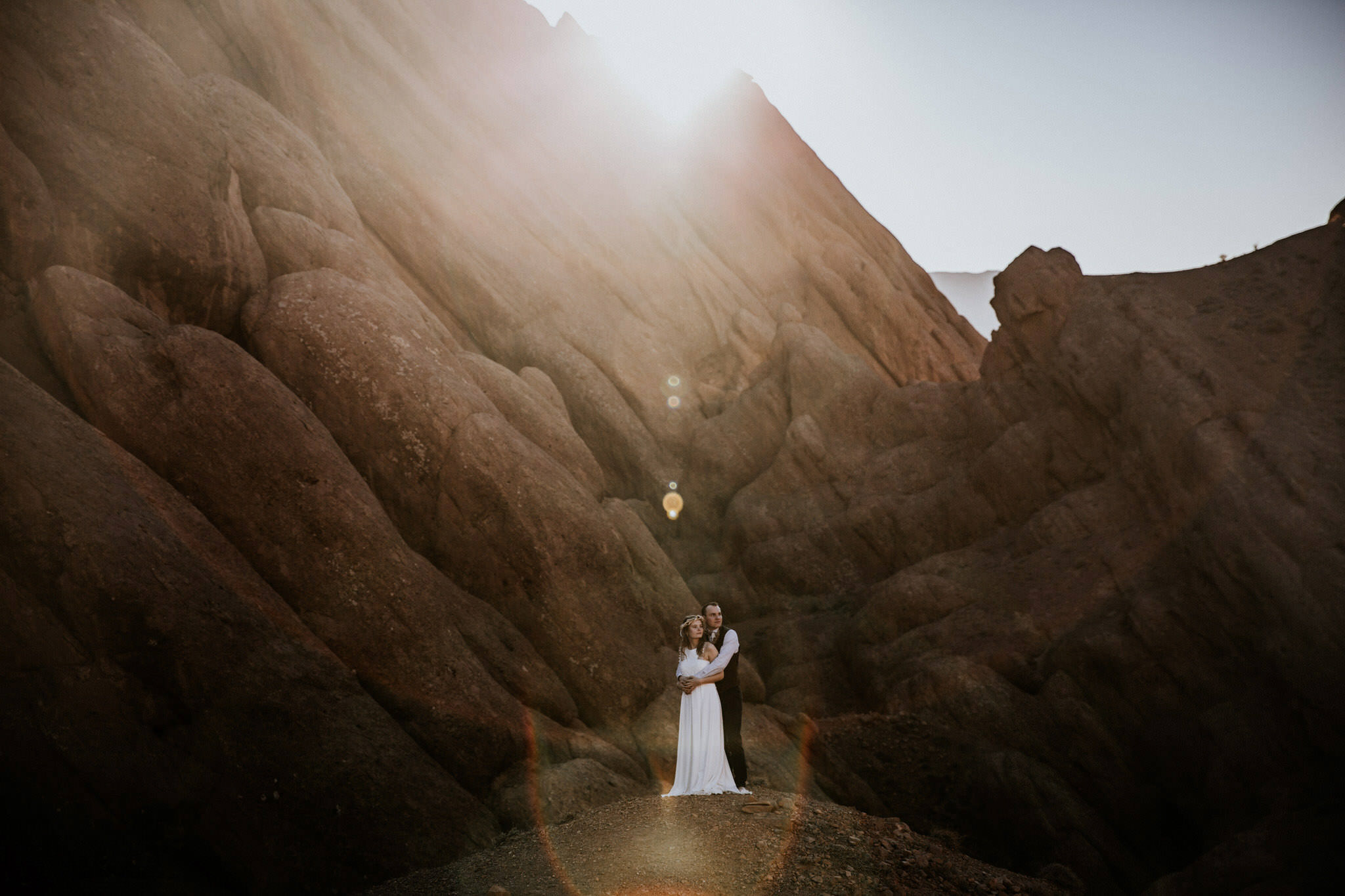 Bride and groom standing on a rocky mountain platform in the sunshine - elopement in the Atlas Mountains, Morocco