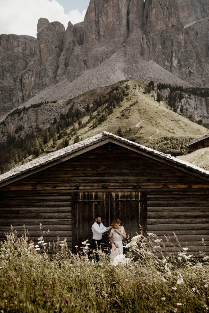 A groom is helping his bride get her eloping dress on, in front of an alpine hut, with the meadows and mountains of Passo Gardena as a gorgeous backdrop