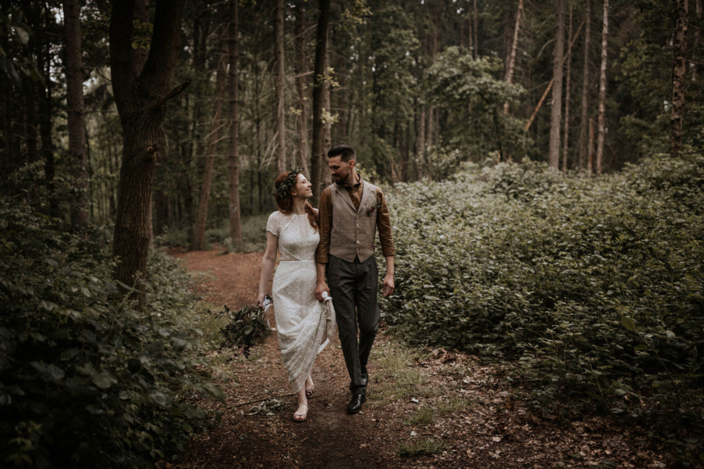 A bride and groom walking hand in hand in rustic Scottish woodland scenery