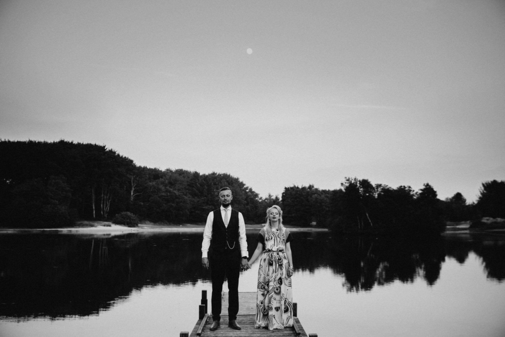 Bride and groom standing hand in hand by a lake under the full moon on their elopement in Schiermonnikoog Island, The Netherlands