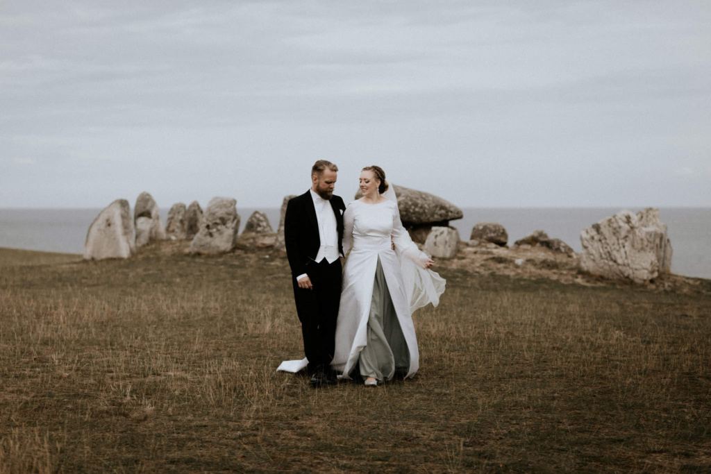 A newly married couple in a coastal field with standing stones, at the coastline of Osterlen, Sweden