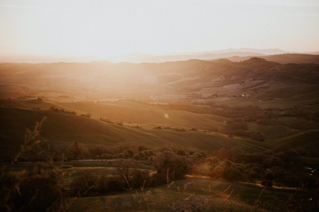 A hazy golden sunset over rolling fields in the Maremma region of Italy