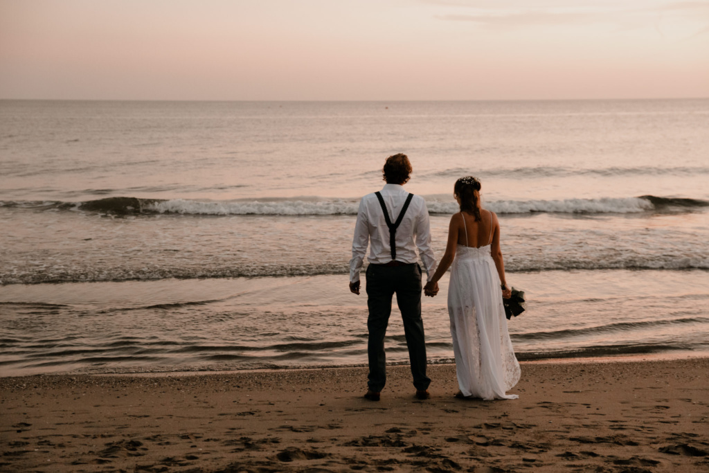 Eloping couple stand on the beach and gaze over the ocean at the Costa del Sol in Spain