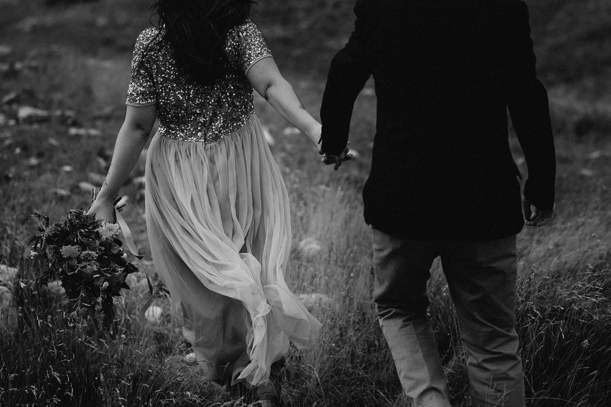 Black and white photo of a couple walking hand in hand through an alpine meadow, seen from behind.