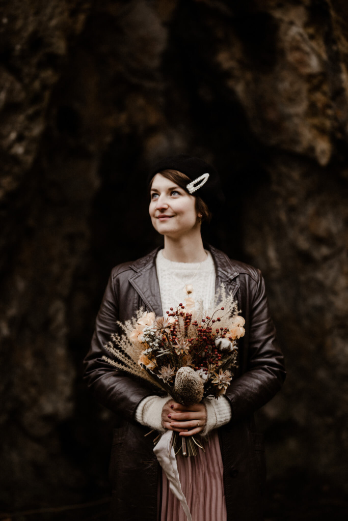 A bride holds her flowers and smiles upwards